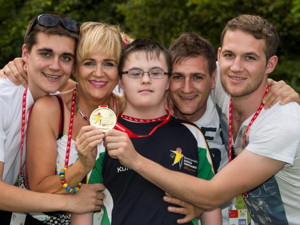 Athlete with family holding up medal