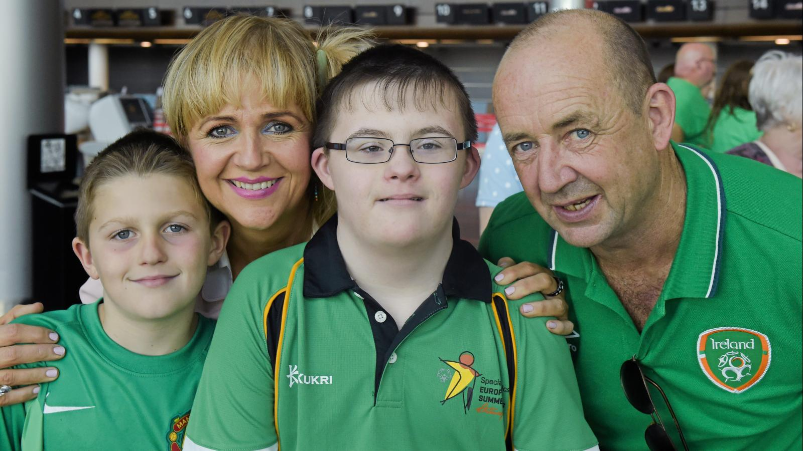 Smiling Family - Special Olympics athlete pictured with his Mum and Dad and younger brother