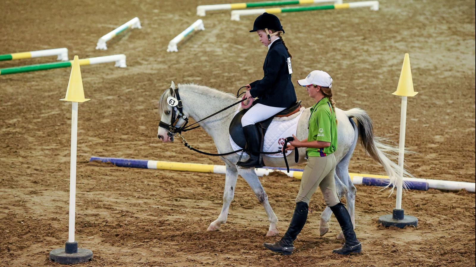 Girl riding horse around arena during competition