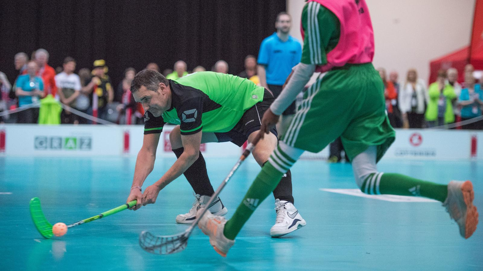 Floorball player striking ball past opponent with audience in background