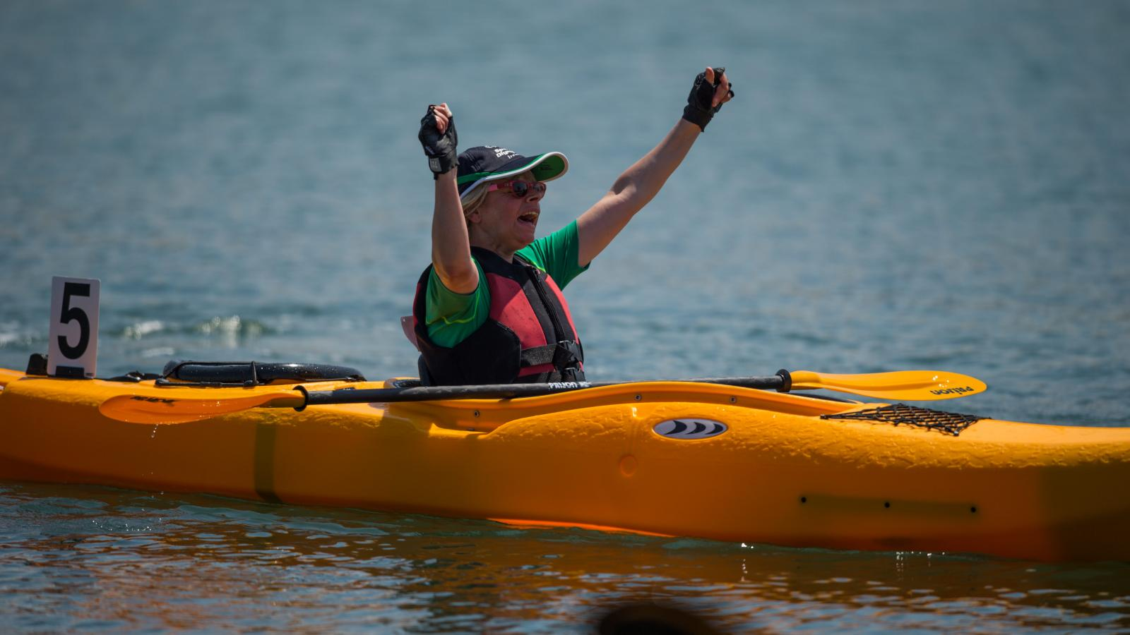 Athlete with arms raised in celebration whilst sitting in kayak