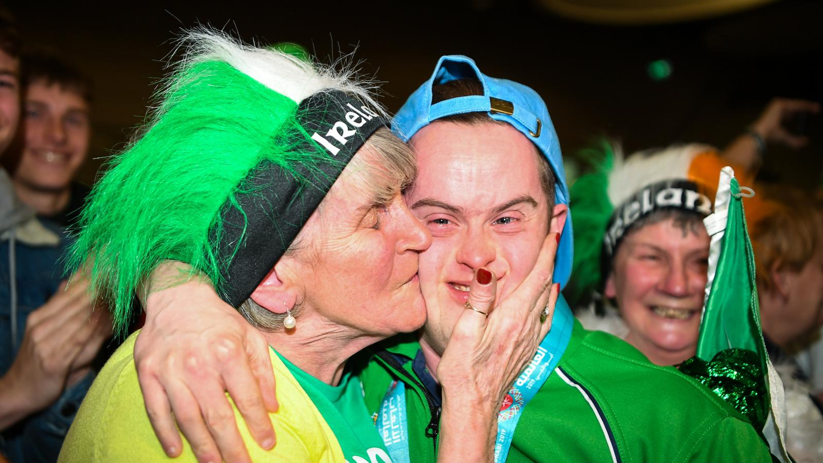 Mother kissing Special Olympics athlete on cheek
