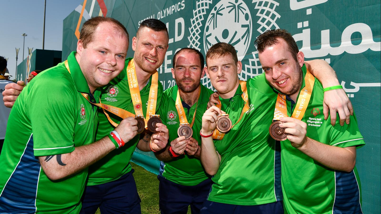 Members of Special Olympics Ireland team holding up medals in celebration